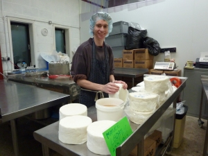 Andrew smiling happily for the camera whilst bandaging cheese