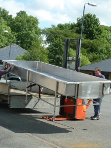 The tricky job of getting the curd table off the trailer and into the dairy